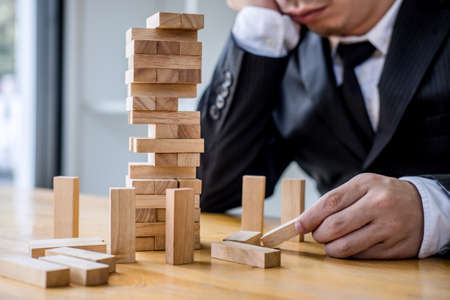 Images of hand of businesspeople placing and pulling wood block on the tower, Alternative risk concept, plan and strategy in business, Risk To Make Business Growth Concept With Wooden Blocks. Foto de archivo