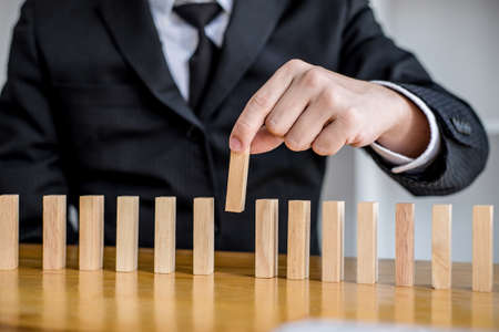 Wooden game strategy, Risk and strategy in business, Close up of businessman hand gambling placing wooden block on a line of domino. Foto de archivo
