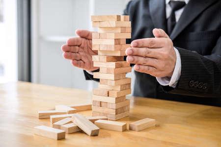 Il concetto di rischio alternativo, il piano e la strategia nel business proteggono con l'equilibrio della pila di legno con la forma del rischio del controllo manuale. Archivio Fotografico