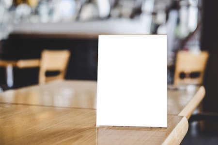 Simulacros de fondo de formularios de plantilla de patrón de carteles de marco acrílico, marco de menú en blanco en la mesa en el soporte de la cafetería para que el texto muestre su producto.