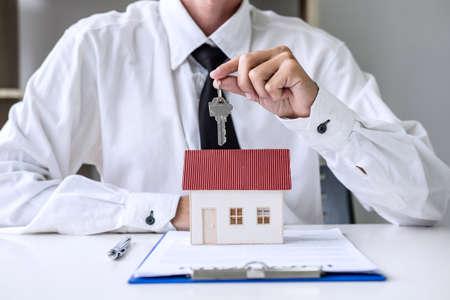 Agente de bienes raíces Gerente de ventas que tiene las llaves de presentación para el cliente después de firmar el contrato de arrendamiento de alquiler o el contrato de compraventa, en relación con la oferta de préstamo hipotecario y el seguro de la casa. Foto de archivo