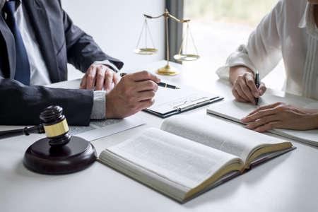 Beratung und Konferenz von professionellen Geschäftsfrauen und männlichen Anwälten, die in einer Anwaltskanzlei im Amt arbeiten und diskutieren. Rechtsbegriffe, Richterhammer mit Waagen der Gerechtigkeit.