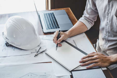 Construction and structure concept of engineer or architect working on blueprint, Engineer working with engineering tools for architectural project on workplace, building project, blueprints.