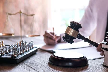 Rechtsrecht, Beratung und Justizkonzept, professionelle männliche Anwälte, die im Gerichtssaal am Tisch sitzen und Papiere mit Hammer und Waage der Gerechtigkeit unterschreiben.