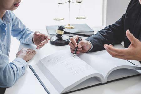 Consulta y conferencia de abogados masculinos y empresaria profesional que trabaja y debate en el bufete de abogados en la oficina. Conceptos de derecho, mazo de juez con balanza de justicia. Foto de archivo