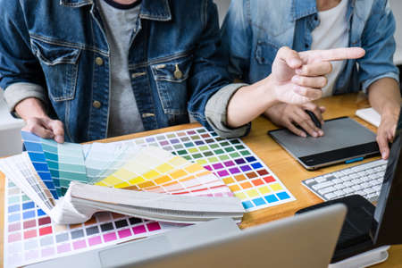Two colleagues creative graphic designer working on color selection and drawing on graphics tablet at workplace, Color swatch samples chart for selection coloring.