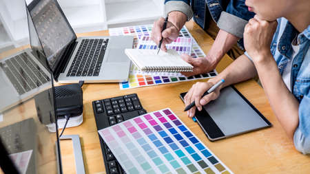 Team of young colleagues creative graphic designer working on color selection and drawing on graphics tablet at workplace, Color swatch samples chart for selection coloring. Stock Photo