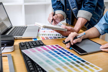 Young creative team having a meeting in creative office, Architectural drawing with work tools and accessories, Color swatch samples chart for selection coloring.