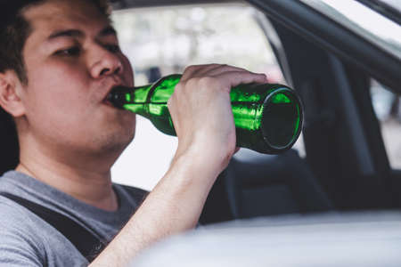 Young asian man drives a car with drunk a bottle of beer behind the wheel of a car. Stock Photo