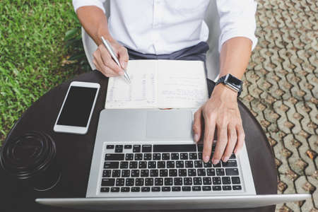Image of businessman working with laptop and analysis financial document data on table in outdoor office, finance,investment, business concept and Accounting,Economic,commercial. Banco de Imagens