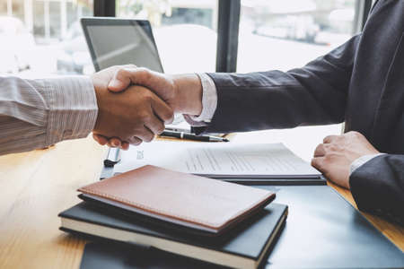 Greeting new colleagues, Handshake while job interviewing, male candidate shaking hands with Interviewer or employer after a job interview, employment and recruitment concept.
