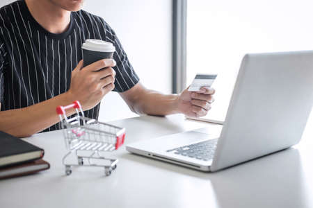 Image of Young man using smartphone for online shopping website and pay by credit card, Online payment and shopping concept. Stock Photo