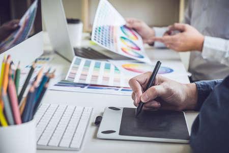 Kreativer Grafikdesigner mit zwei Kollegen, der an Farbauswahl und Farbfeldern arbeitet und auf einem Grafiktablett am Arbeitsplatz mit Arbeitswerkzeugen und Zubehör zeichnet. Standard-Bild