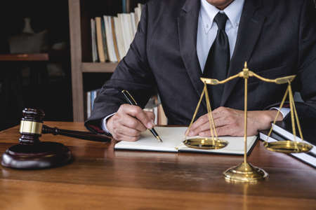 Legal law, advice and justice concept, Judge gavel with Justice lawyers, Counselor in suit or lawyer working on a documents in courtroom. Stock Photo