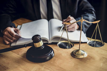 Male lawyer or judge working with contract papers, Law books and wooden gavel on table in courtroom, Justice lawyers at law firm, Law and Legal services concept. Stock Photo