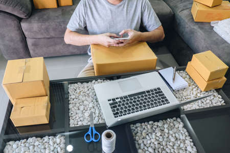 Small business parcel for shipment to client at home, Young entrepreneur SME freelance man working online business by using smart phone with making on purchase order and preparing package product. Stock Photo