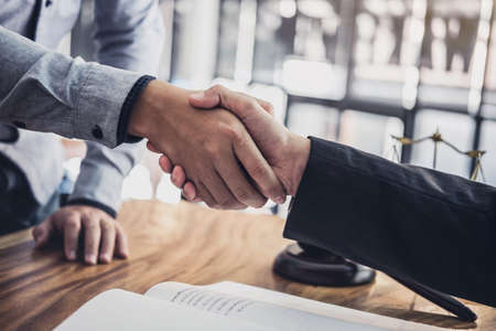 Handshake after good cooperation, Businessman Shaking hands with Professional male lawyer after discussing good deal of contract in courtroom.