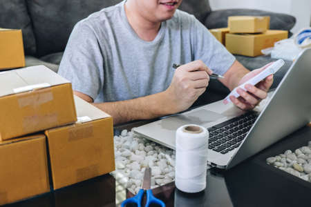 Small business parcel for shipment to client at home, Young entrepreneur SME freelance man working with note packaging sort box delivery online market on purchase order and preparing package product.