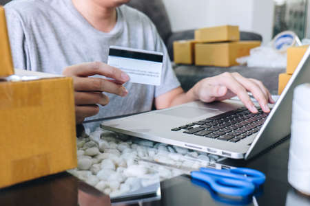 Small business parcel for shipment to client, Young man received online shopping parcel opening boxes and buying items by credit card, online marketing on purchase order package product. Stock Photo