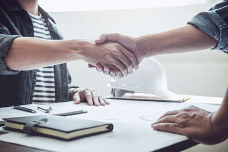Finishing up a meeting, Two engineer or architect meeting for project, handshake after consultation and conference new project plan, contract for both companies, success, partnership. Stock Photo