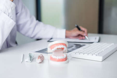 Male doctor or dentist working with patient tooth x-ray film, model and equipment used in the treatment and analysis teeth disease of dental and dentistry at workplace.