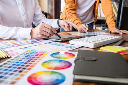 Two colleagues creative graphic designer working on color selection and drawing on graphics tablet at workplace. Stock Photo - 128808928