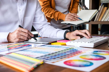 Two colleagues creative graphic designer working on color selection and drawing on graphics tablet at workplace. Stock Photo - 128808929