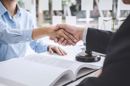 Handshake after good cooperation, Businesswoman Shaking hands with Professional male lawyer after discussing good deal of contract in courtroom, Concepts of law, Judge gavel with scales of justice. Stock Photo - 128809201
