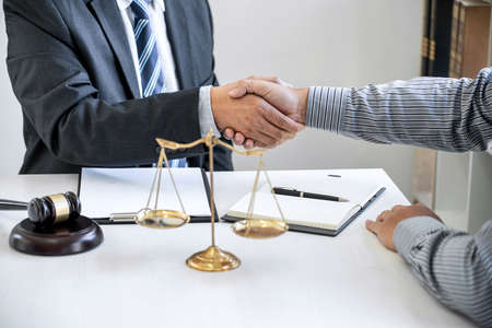 Handshake after good cooperation, Businessman Shaking hands with Professional male lawyer after discussing good deal of contract in courtroom, Concepts of law, Judge gavel with scales of justice.