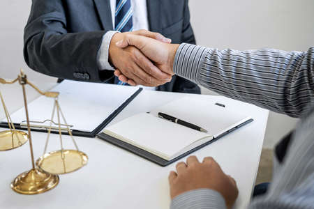 Handshake after good cooperation, Businessman Shaking hands with Professional male lawyer after discussing good deal of contract in courtroom, Concepts of law, Judge gavel with scales of justice. Stock Photo