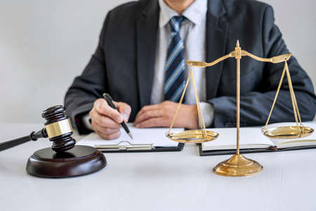 Male lawyer or judge working with contract papers, Law books and wooden gavel on table in courtroom, Justice lawyers at law firm, Law and Legal services concept. Stock fotó
