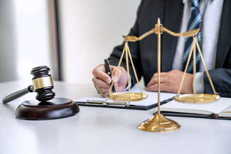 Male lawyer or judge working with contract papers, Law books and wooden gavel on table in courtroom, Justice lawyers at law firm, Law and Legal services concept. Stok Fotoğraf