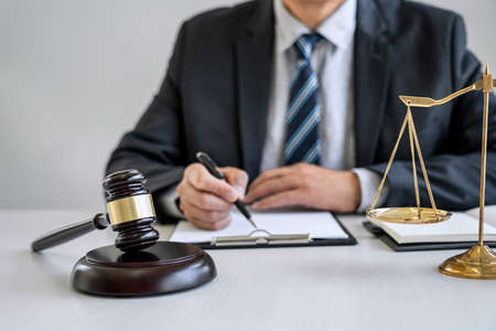 Male lawyer or judge working with contract papers, Law books and wooden gavel on table in courtroom, Justice lawyers at law firm, Law and Legal services concept. Banque d'images