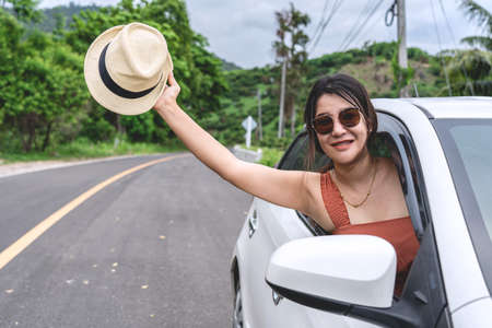 Relaxed happy traveler, Young beautiful girl holding white hat weave and Reach out of the car at sunshine and nature view with mountain road background. Stock fotó