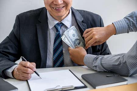 Concept de corruption et de corruption, pot-de-vin sous forme de billets d'un dollar, homme d'affaires donnant de l'argent dans l'enveloppe tout en concluant un accord sur un contrat immobilier et financier.