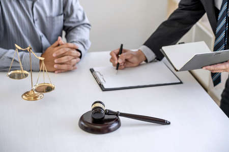 Consultation and conference of Male lawyers and professional businessman working and discussion having at law firm in office. Concepts of law, Judge gavel with scales of justice..