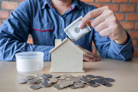 Man putting coins into money box with savings and analysis business investment strategy home loan with income of money coin and dollar for future real estate.