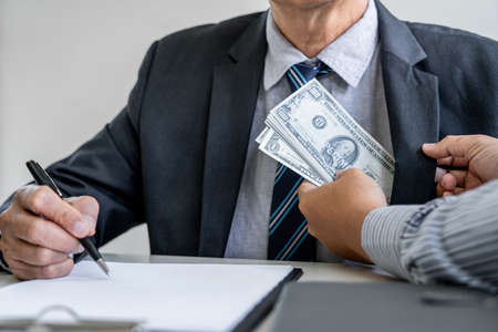Bribery and corruption concept, bribe in the form of dollar bills, consultant receive money from businessman while making deal to agreement a real estate corporate contract and financial.