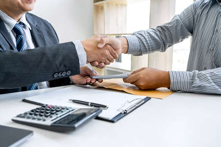 Bribery and corruption concept, bribe in the form of dollar bills, Businessman shaking hands and giving hides money while making deal to agreement a contract.