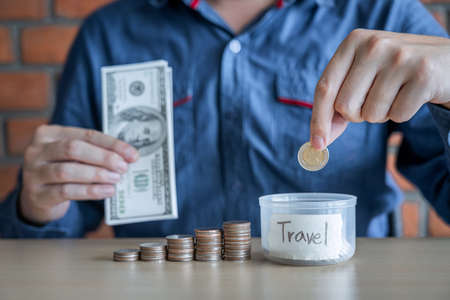 Man putting coins into money box with savings and analysis business investment strategy with income of money coin for future travel, retirement financial concept.