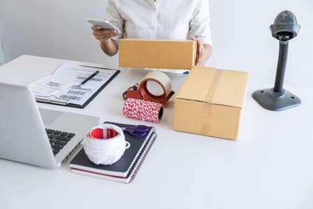 Young entrepreneur SME freelance using smartphone receive order client and take note working with packaging sort box delivery online market on purchase order and preparing package product.