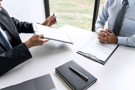 Senior committee manager reading a resume during a job interview, Employer interviewing to ask young male job seeker for recruitment talking in office.