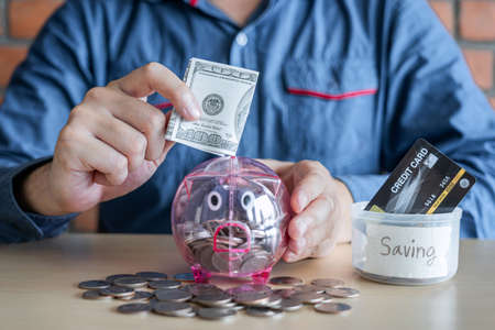 Man putting coins into piggy bank with savings and analysis business investment strategy with income of money coin and dollar for future retirement financial concept.