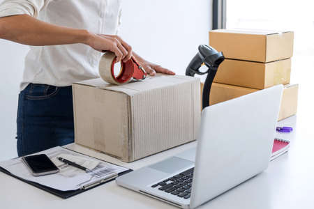 Shipment Online Sales, Small business or SME entrepreneur owner delivery service and working packing box, business owner working checking order to confirm before sending customer in post office.
