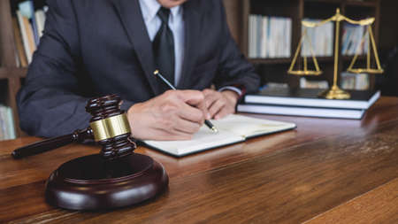 Legal law, advice and justice concept, Judge gavel with Justice lawyers, Counselor in suit or lawyer working on a documents in courtroom. 免版税图像
