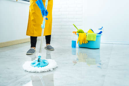 Concept de ménage et de nettoyage d'épouse, jeune femme heureuse dans des gants en caoutchouc bleus essuyant la poussière à l'aide d'une vadrouille tout en nettoyant le sol à la maison.