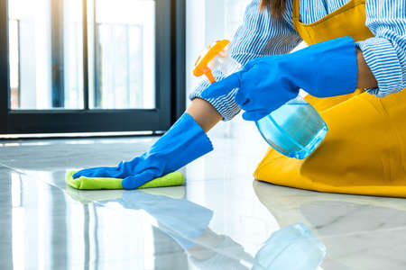 Wife housekeeping and cleaning concept, Happy young woman in blue rubber gloves wiping dust using a spray and a duster while cleaning on floor at home. Reklamní fotografie