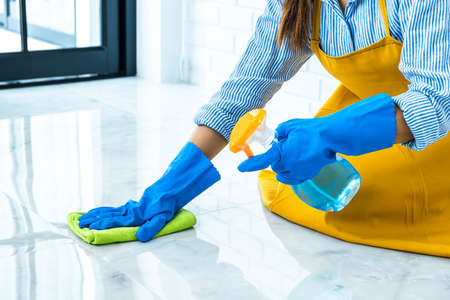 Wife housekeeping and cleaning concept, Happy young woman in blue rubber gloves wiping dust using a spray and a duster while cleaning on floor at home.