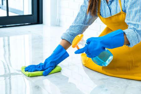 Concetto di pulizia e pulizia della moglie, giovane donna felice in guanti di gomma blu che pulisce la polvere usando uno spray e uno spolverino durante la pulizia sul pavimento di casa.