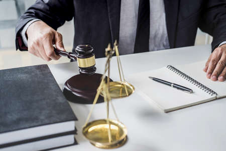 Male lawyer or judge working with contract papers, Law books and wooden gavel on table in courtroom, Justice lawyers at law firm, Law and Legal services concept. 版權商用圖片